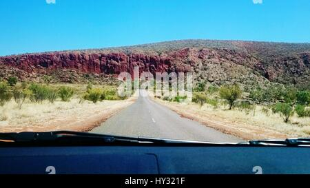 Road Amidst Trees Against Clear Sky Seen Through Car Windshield - Stock Image