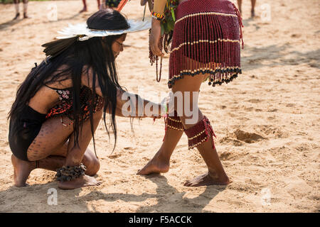 Palmas, Tocantins State, Brazil. 29th October, 2015. An indigenous Brazilan girl ties a beaded anklet round the - Stock Image
