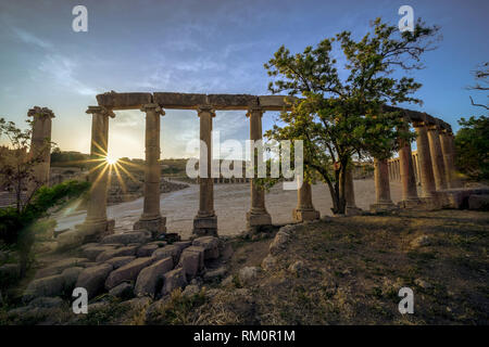 Rays of light burst from behind the Ionic colonnade of the Roman forum in the ancient city of Jerash in modern day Jordan. - Stock Image