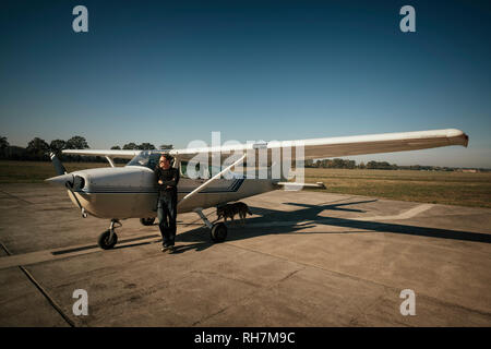 Male pilot standing at small propellor airplane on sunny tarmac - Stock Image
