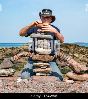 Dunbar, East Lothian, Scotland, UK. 21st Apr 2019. European stone stacking championship: Harry Maddox, from England, balances stones in the artistic competition, giving competitors 3 hours to create anything from stones or found objects at Eye Cave beach on the second day which comprises 2 competitions, a 3 hour artistic challenge and a children's competition. The overall winner receives a trip to llano Earth Art Festival & World Stone Balancing competition in Texas in 2020. Credit: Sally Anderson/Alamy Live News - Stock Image