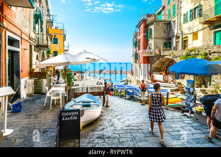 Tourists enjoy a sunny day on the Ligurian coast with the sea, cafe and boats in Riomaggiore Italy, on the Cinque Terre of the Italian Riviera - Stock Image
