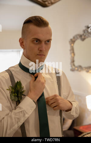 Groom prepares for his Wedding in front of mirror, Jennycliff, Plymouth, Devon, UK - Stock Image
