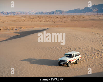 Yazd, Iran - March 8, 2017 : Off orad vehicle on sand dunes. Desert tours are a popular tourist activity in Yazd, southern Iran - Stock Image