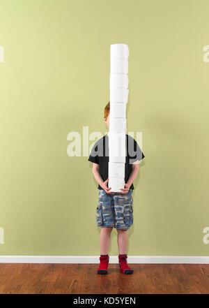 boy 4-7 balancing stack of toilet paper - Stock Image