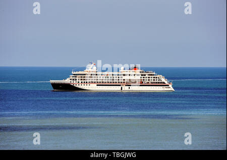 Cruise ship at sea, large luxury white cruise ship liner on blue sea water and blue sky background. - Stock Image