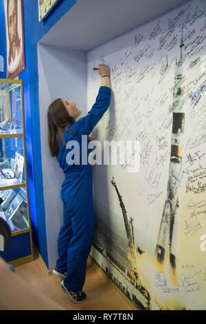 International Space Station Expedition 59 crew member Christina Koch of NASA signs a wall mural bearing the names of those who have flown in space at the Baikonur Cosmodrome March 10, 2019 in Baikonur, Kazakhstan. Expedition 59 crew: Christina Koch of NASA, Alexey Ovchinin of Roscosmos, and Nick Hague of NASA will launch March 14th onboard the Soyuz MS-12 spacecraft for a six-and-a-half month mission on the International Space Station. - Stock Image