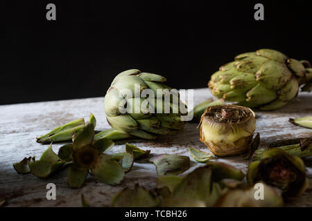 closeup of some whole raw fresh artichokes and some other cut artichokes and their leaves on a white rustic wooden table, against a black background - Stock Image