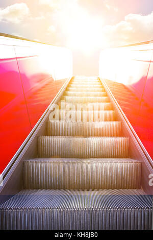 Ascending on a moving stairway or escalator into sunlight. Concept photo for success and a bright future. - Stock Image