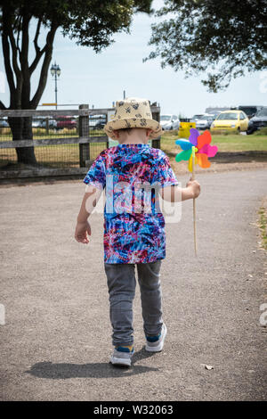A small boy running through a park holding a multi coloured windmill - Stock Image