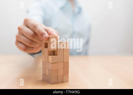 Man's hand adding the last missing wooden block into place. Business success concept. - Stock Image