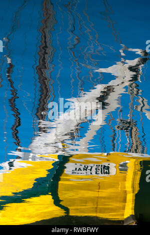 France, 2018, Reflection of moored fishing boats on the harbour's water. - Stock Image