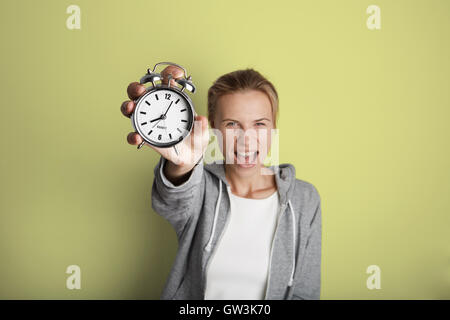Portrait Handsome Young Woman Posing Blank Yellow Background.Pretty Girl Screaming Holding Vintage Alarm Clock Hand - Stock Image
