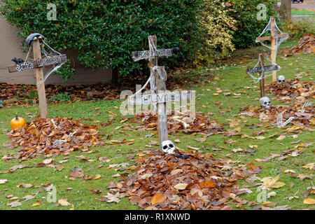 Graves and skulls Halloween decorations on the front lawn of a house - Stock Image
