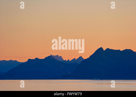 Silhouettes of craggy mountains at sunset near Henningsvae ron Lofoten in northern Norway. - Stock Image