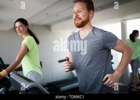 People running on a treadmill in health club - Stock Image