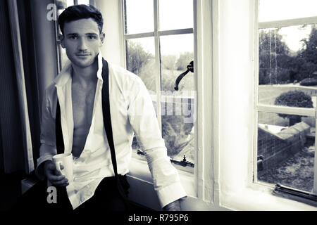 Attractive man sitting in hotel room window enjoying a beverage in a white mug - Stock Image