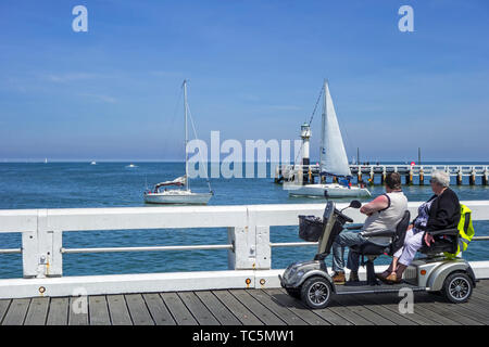 Disabled pensioners in duo two person mobility scooter watching sailing boats at sea from jetty at seaside resort in summer - Stock Image