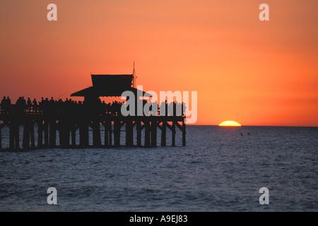 Florida Naples Pier Sunset crowd of people on pier silhouette orange sky - Stock Image