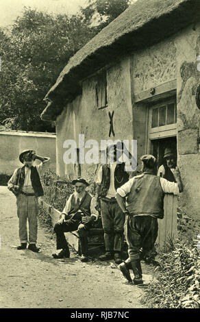 Men drinking beer after a day's work, haymaking in the fields, in the West Country village of Bradford Peverell, Dorset, an English county which inspired the writings of the novelist Thomas Hardy and the poet William Barnes. - Stock Image