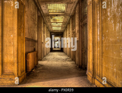 Interior view of a concrete hallway in an abandoned office building in France. - Stock Image
