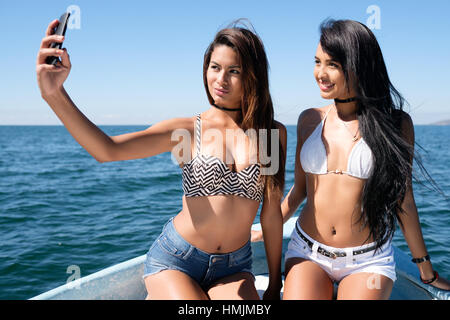 Two very attractive young hispanic women taking a cell phone selfie photo on a boat - Stock Image