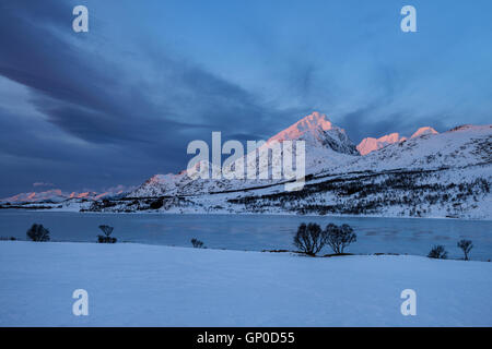 First light illuminating Ristind mountain peak, Vestvågøy, Lofoten Islands, Norway - Stock Image