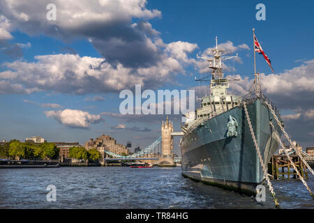 HMS Belfast ship flying Union Jack Flag, moored on River Thames in late afternoon sunlight, with Tower Bridge and The Tower Hotel behind London SE1 - Stock Image