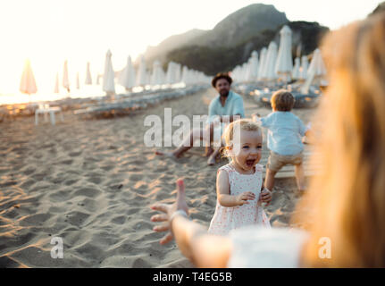 A young family with toddler children having fun on beach on summer holiday. Copy space. - Stock Image
