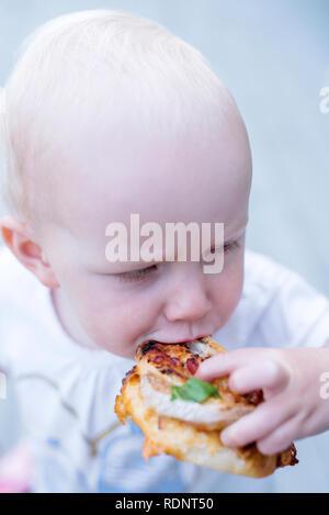 Boy eating grilled bun outdoors - Stock Image