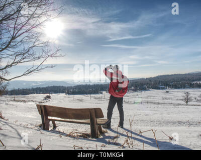 Back view of man hiker with backpack looking to landscape covered snow - Stock Image