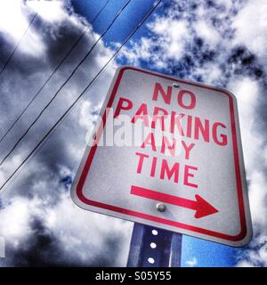 No parking anytime sign with cloudy sky. - Stock Image