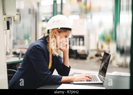 A side view of industrial woman engineer in a factory using laptop and smartphone. - Stock Image