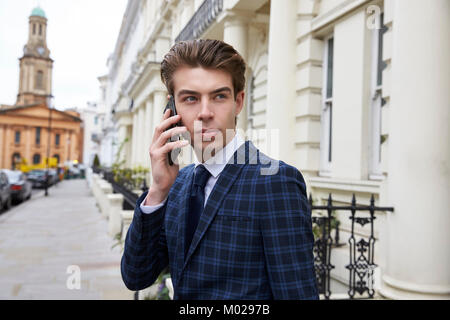 Young man in checked suit using phone in street, waist up - Stock Image