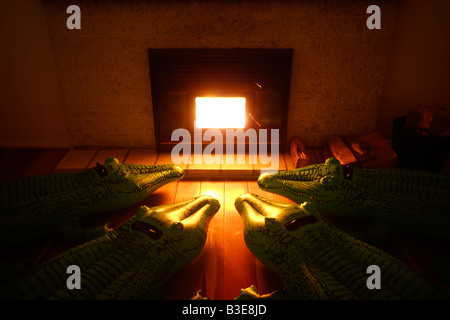 Inflatable crocodile series Huddle by the fireplace - Stock Image