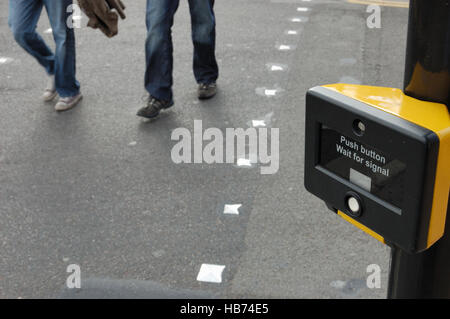 People walking across a pedestrian crossing.  Focus on the crossing sign. - Stock Image