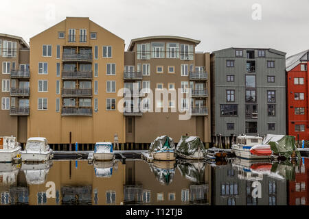 Small boats in front of  buildings on the edge of river channels in the town of Trondheim in Norway. - Stock Image