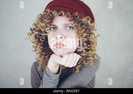 Close-up portrait of a beautiful and young funny bored or angry woman with blue eyes and curly blonde hair wearing a red woolen cap - Stock Image