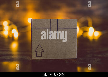 cardboard delivery parcel box on wooden desk and fairy lights in the background, concept of shipping and handling - Stock Image