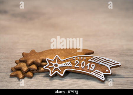 Still life with ornate New Year Bethlehem star on a wood background. Decorated Xmas gingerbread laid on stacked golden sweets. For good luck in 2019. - Stock Image