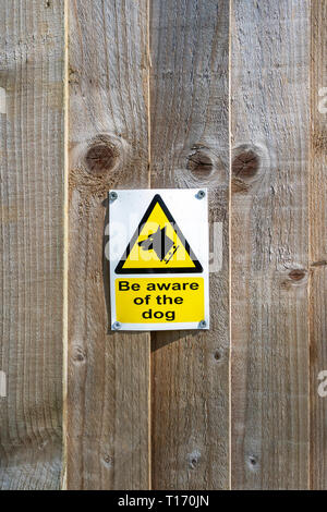 Beware of the dog sign on wooden fence - Stock Image