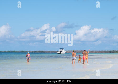 Young family enjoys the warm clear blue water of the Bay of Pigs in Cuba. - Stock Image