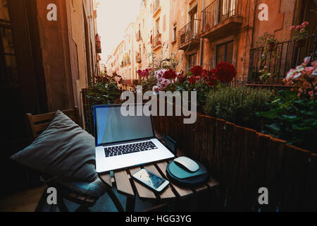 Cozy beautiful workspace on balcony with laptop, smartphone, wooden fence and a lot of flowers around on sunny summer - Stock Image