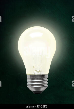 Glowing electrical incandescent light bulb isolated on chalkboard background with copy space. - Stock Image