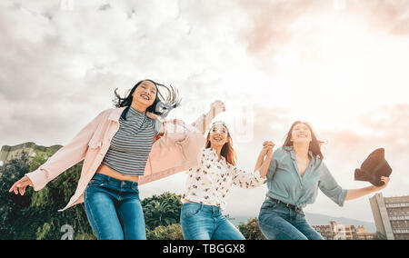 Happy Asian girls jumping outdoor - Young women friends having fun during university break - Stock Image