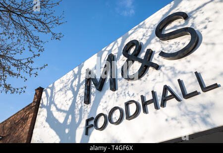 Exterior of a Marks And Spencer food hall with tree shadows. - Stock Image