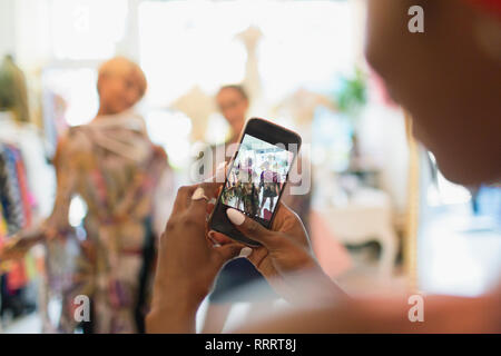Young woman with camera phone photographing friends shopping in store - Stock Image