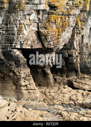 Eroded rocks sea cliffs and sea caves on shoreline near Elgol on the Scottish Island of Skye, Scotland, UK - Stock Image