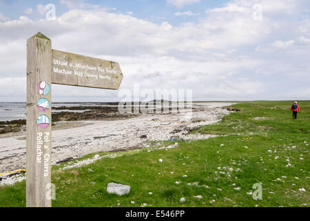Machair Way walk signpost with walker going north on coast near Pollachar South Uist Outer Hebrides Western Isles - Stock Image
