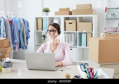 Young smiling helpdesk manager talking to clients online while taking their orders - Stock Image